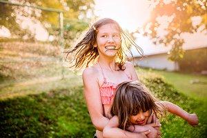 Two cute girls having fun outside in summer garden