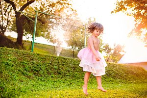 Girl in princess skirt jumping in sunny summer garden