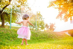 Girl in princess skirt running in sunny summer garden