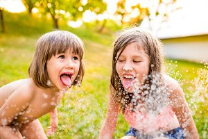 Two girls at the sprinkler, sunny summer in the garden