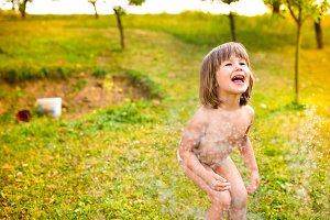 Little girl at the sprinkler having fun, summer garden