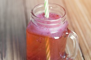 Red lemonade with raspberry on woode
