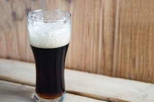 A glass of cold dark beer on a woode