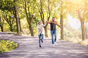 Couple in love  in park on a walk, running