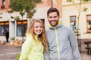 Young couple running in the city, resting, pausing