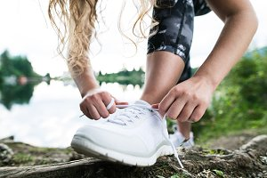 Close up of an unrecognizable young runner tying shoelaces