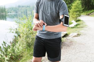 Young runner with smart watch and smart phone. Green nature.