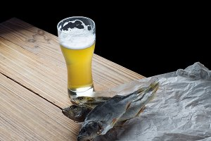Beer with dried fish on a wooden tab