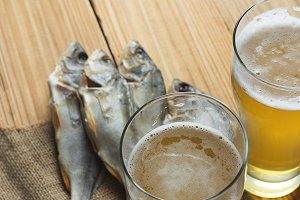Dried fish with beer on wooden backg