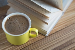 A Cup of cappuccino with a book in t