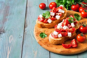 Italian bruschetta with tomato and cheese on toasted toast, blue wooden background. Copy space, selective focus.