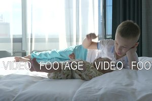 Boy and baby sister on the bed at home