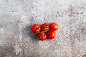 a bunch of red ripe fresh tomato on a stone surface. copy space