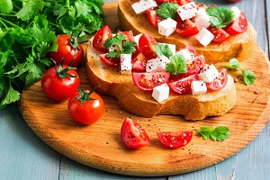 Bruschetta with tomatoes, cheese and greens on toasted bread. Traditional Italian food. Selective focus.