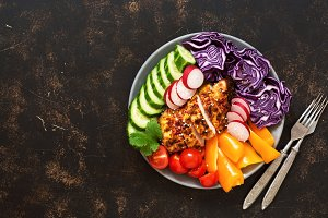 Bowl of buddha with baked chicken fillet and fresh vegetables on a dark background, top view. Copy space.