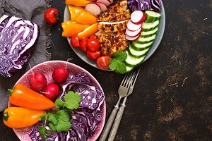 Bowl of buddha with baked chicken fillet and fresh vegetables on a dark background, top view. Copy space