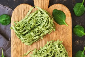 Italian raw pasta with spinach on a cutting Board. The view from the top.