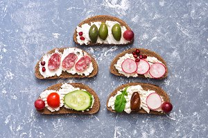 Bruschetta with a variety of filling on a gray background, top view.
