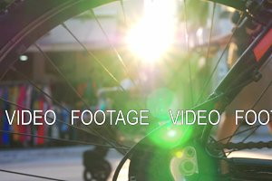 View through bike wheel to street and sun flare