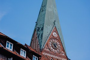 Tower of the St. Johannis church of Luneburg and an old half-timbered red bricks house in front. Germany