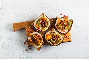 snack breads with hummus and baked pumpkin on a serving board wi