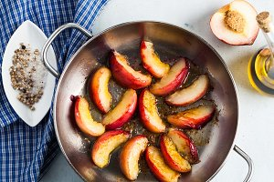 fried pieces of peaches in a frying pan on the table. Cooking.