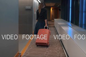 Woman with trolley case in the hotel hallway