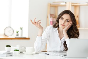 thoughtful woman with hand under chin bored at work, looking away sitting near laptop, demotivated office worker feels lack of inspiration, no motivation