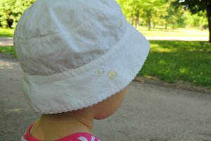 Toddler girl in summer hat.