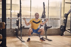 one young smiling man, wearing sport clothes, squat exercise with bar, in old beaten up gym interior. full lenght shot.
