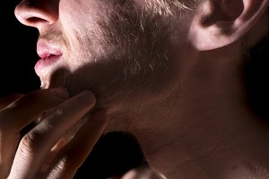 close up man scratching his beard on dark background