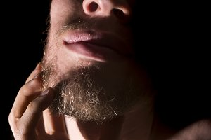 close up isolated man face scratching his beard