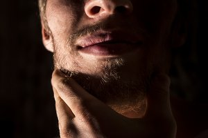 close up portrait of man scratching his beard on a black background