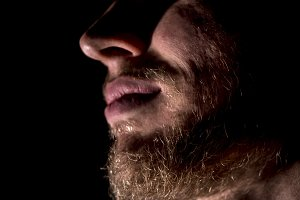 close up part of man face with beard on a black background