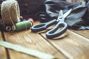 close up scissors tread rolls and cloth os a wooden table