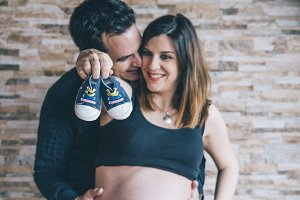 Pregnant mum and dad holding a pair of baby shoes.