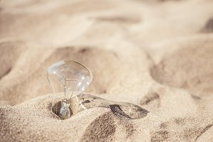 electric lighting lamp covered by sand on the beach