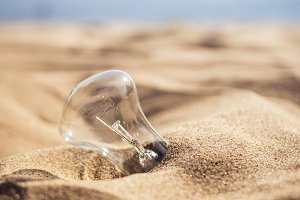 incandescent lamp buried in sand on the beach