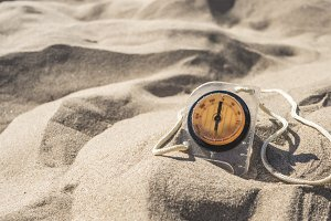 summer travel concept, compass in sand on a sea beach