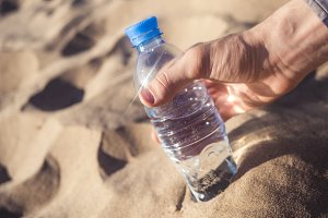 person taking a bottled water on a summer sunny day on a sea sandy beach