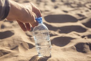 person opens the drinking bottled water in sand on the sea coast