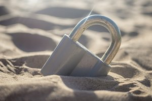 buried locked padlock in sand against the sushine