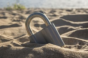 close up metal padlock on the sea coast in sand