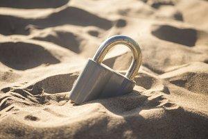 closed locked padlock buried in sand