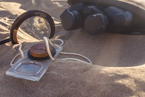 travel supplies on a sandy beach under sunshine