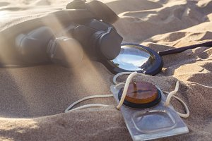 close up compass magnifier and binoculars on the sea sandy coast on a summer sunny day