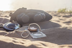 magnifying glass compass and binoculars on the sea sandy beach