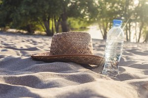 close up drinking water and summer lady hat on the sandy beach in tropics
