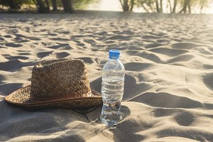 summer tropical exotic beach, bottled water and hat on the sand
