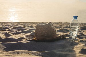 close up summer holiday concept, bottle with water and lady hat on a sunset beach